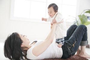 仰向けの母親の上で立つ赤ちゃん