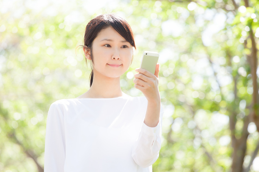 スマートフォンで検索する女性、新緑